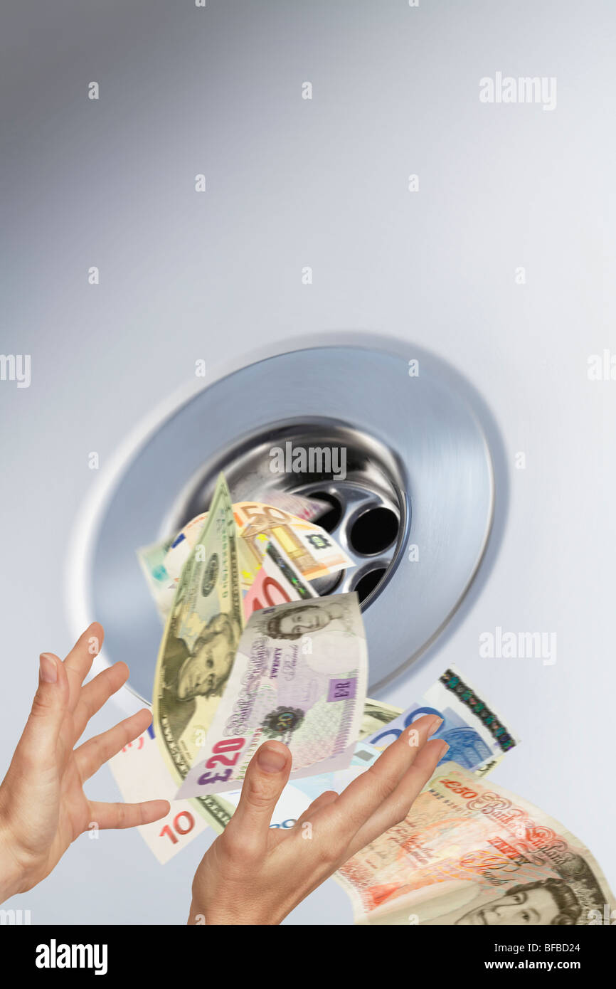 money going down the plughole into sink drain conceptual image - Stock Image