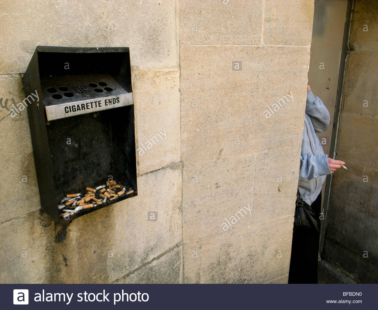 Woman smoking a cigarette in a door way with an ashtray full of butts & Woman smoking a cigarette in a door way with an ashtray full of ...