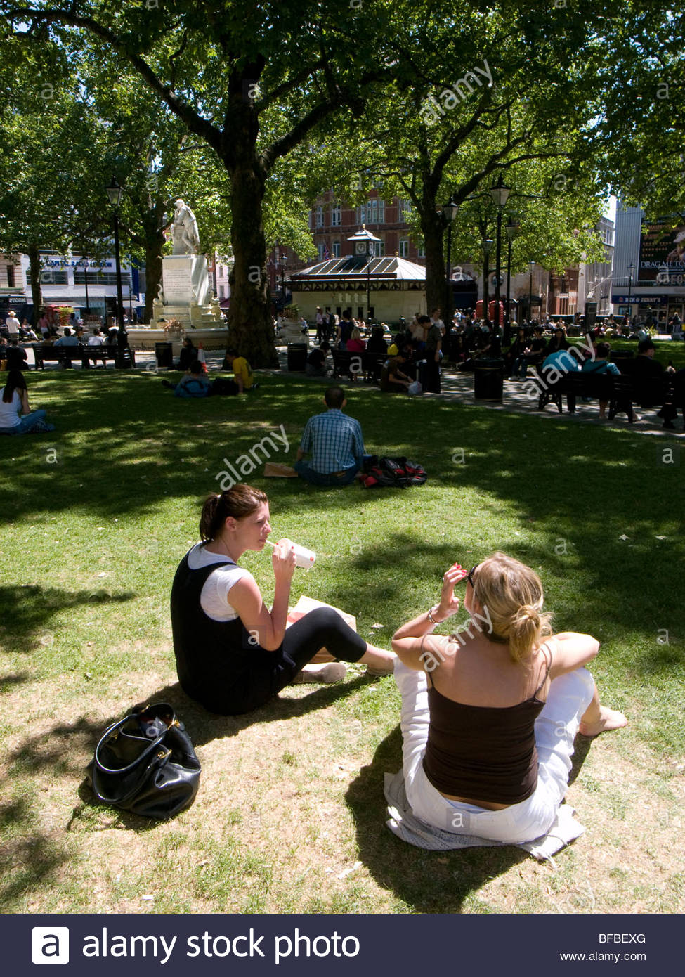 Leicester Square London,girls sitting in Summer Sun - Stock Image