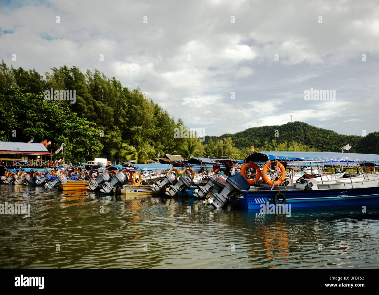 Motor boats moored at a quay in Langkawi in Malaysia.  Photo by Gordon Scammell - Stock Image
