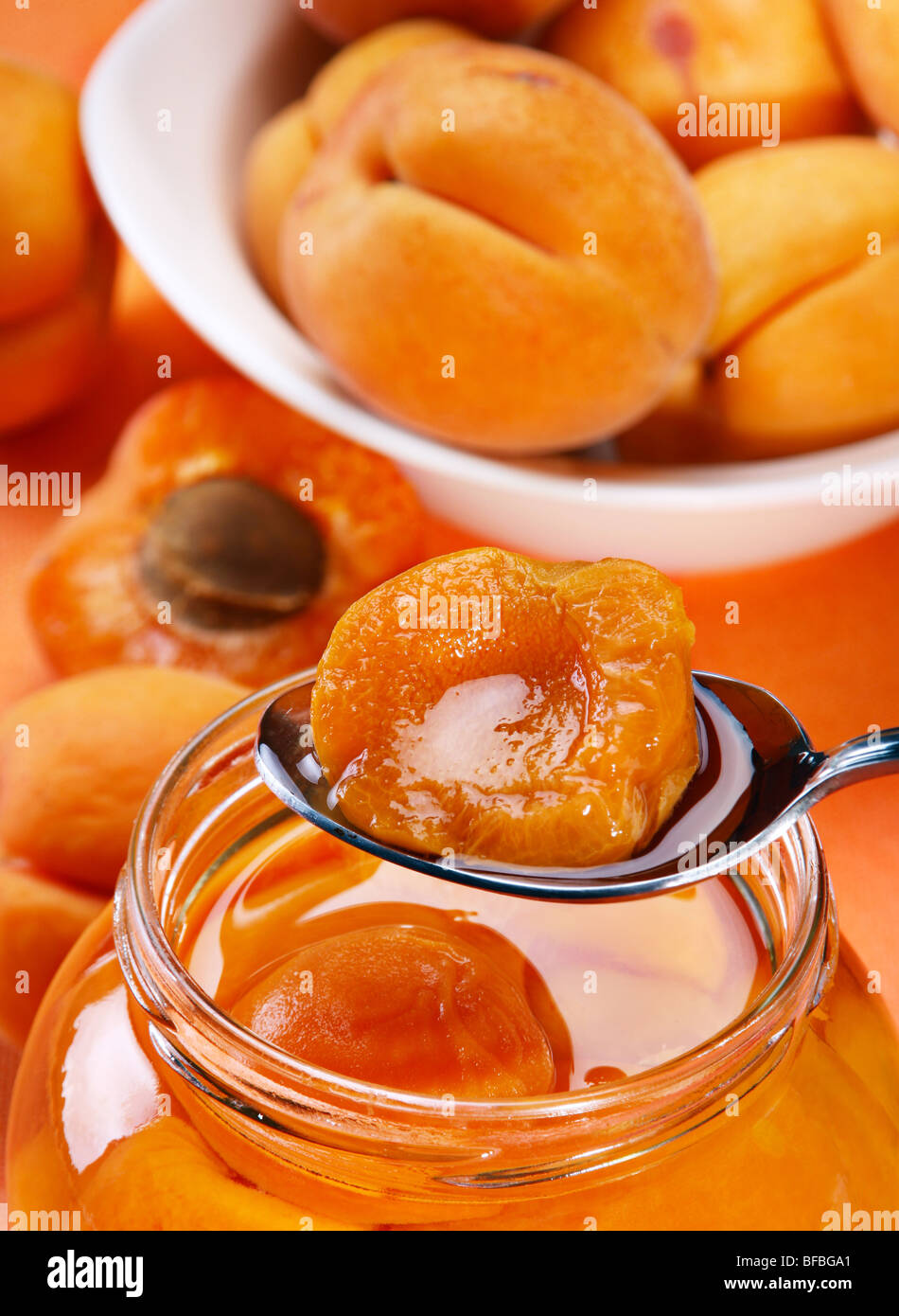 Preserved apricot in spoon with fresh fruit - Stock Image