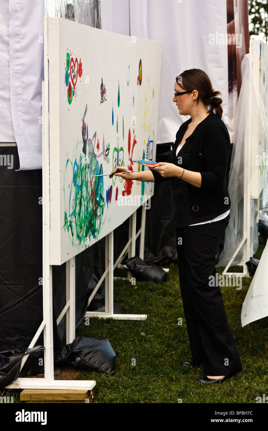 Woman painting a mural/canvas outdoors (Toronto Vichy promotional event) - Stock Image