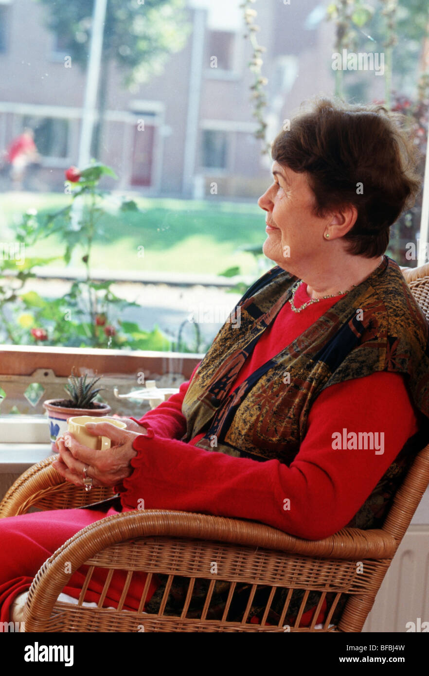 Female pensioner sitting on chair looking out of window, cup of coffee in hands, thinking Stock Photo