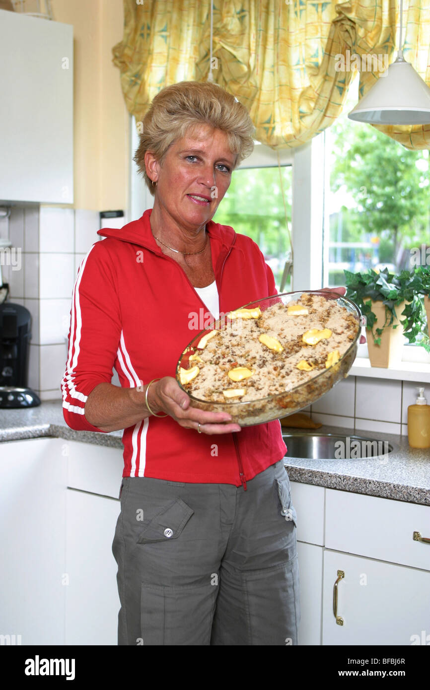 Mature woman showing starchy food meal in kitchen. - Stock Image