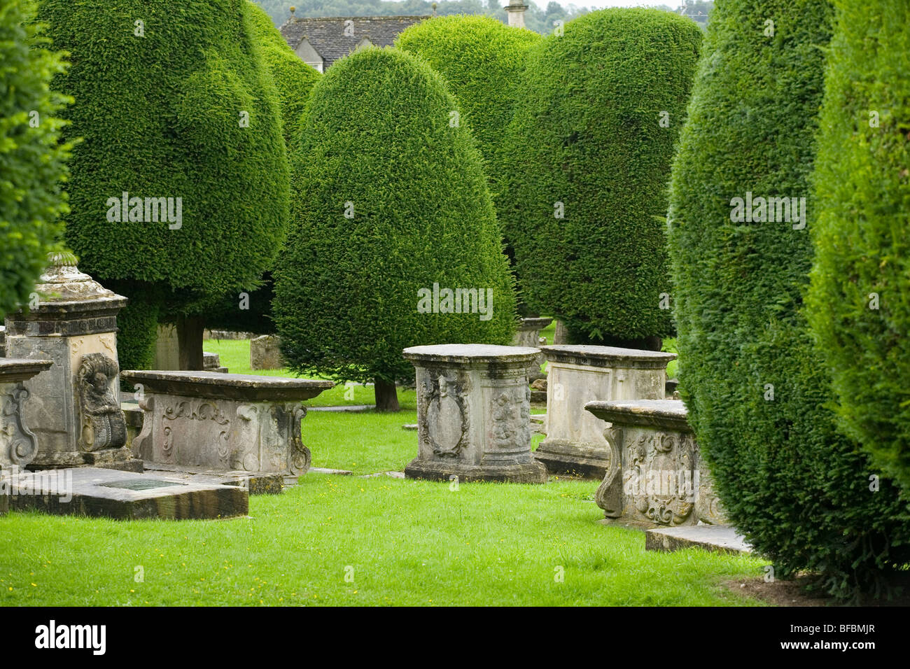 Tombs and yew trees in churchyard of St Mary's Church Painswick England - Stock Image