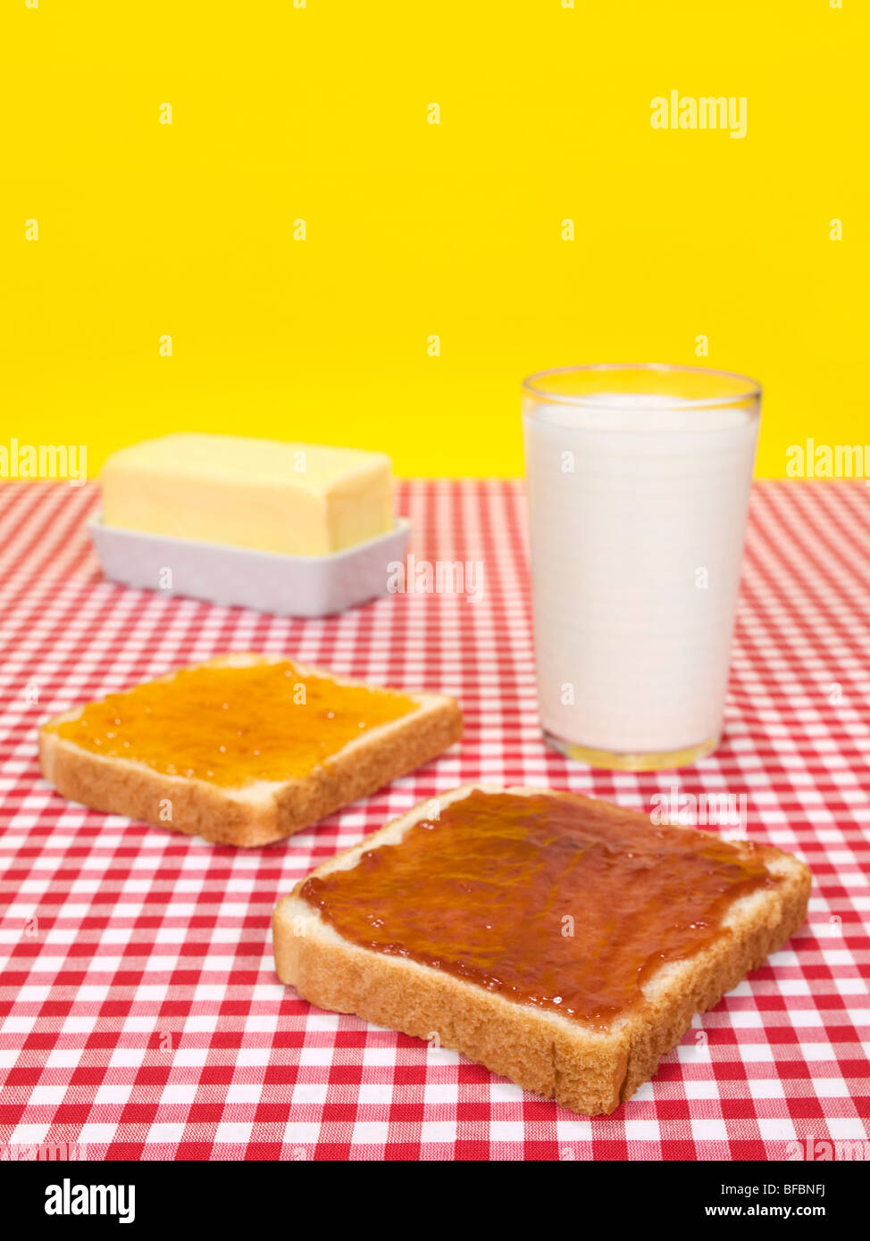 Two slices of bread spread with jam, a glass of milk and a butter stick. Stock Photo