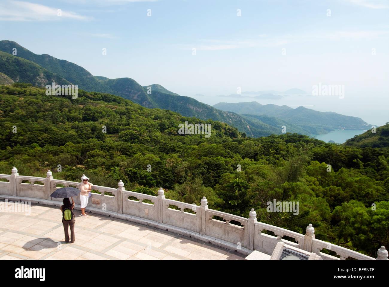 View from Tian Tan Big Buddha with woman posing for a photograph, Lantau island, Hong Kong - Stock Image