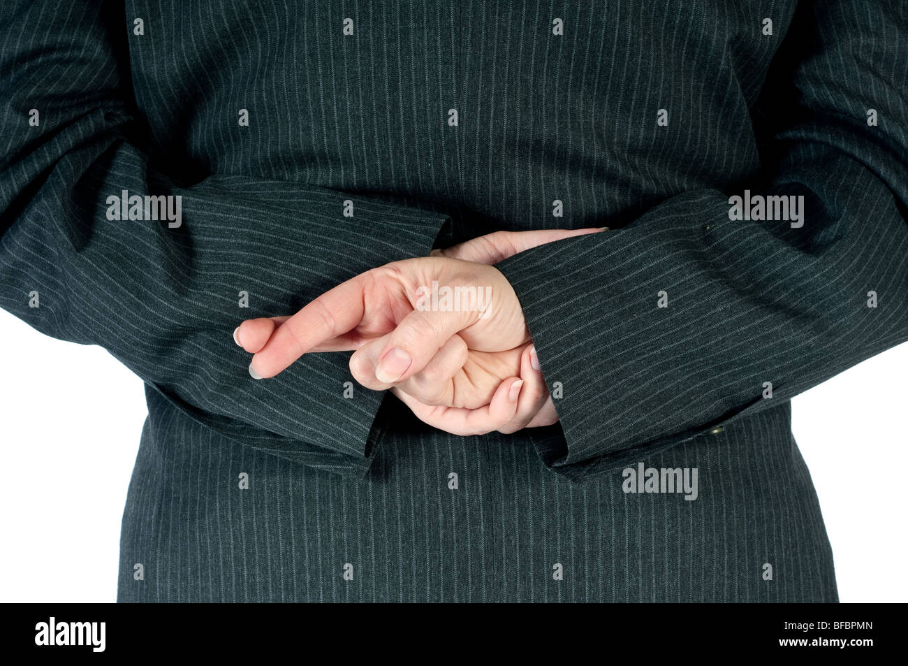 Female business person with fingers crossed behind back - Stock Image