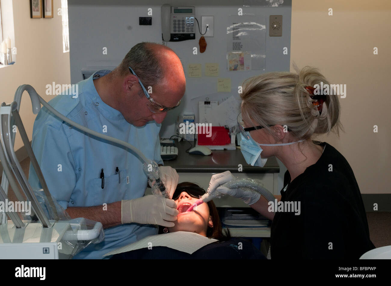 Dentist and dental assistant give a patient in a modern dental surgery a regular checkup - Stock Image