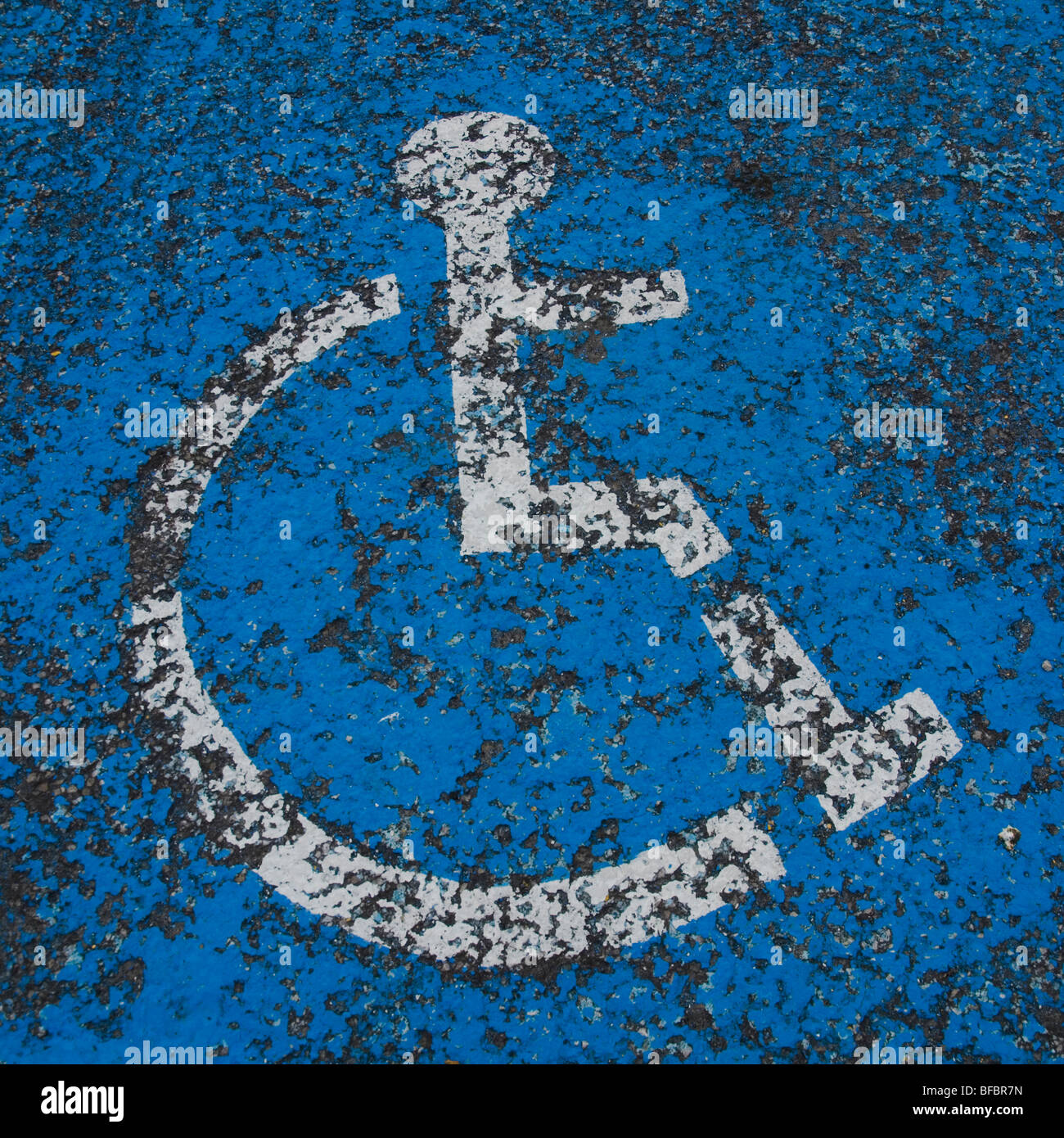 Wheelchair symbol dor disabled parking space painted on tar road surface. - Stock Image