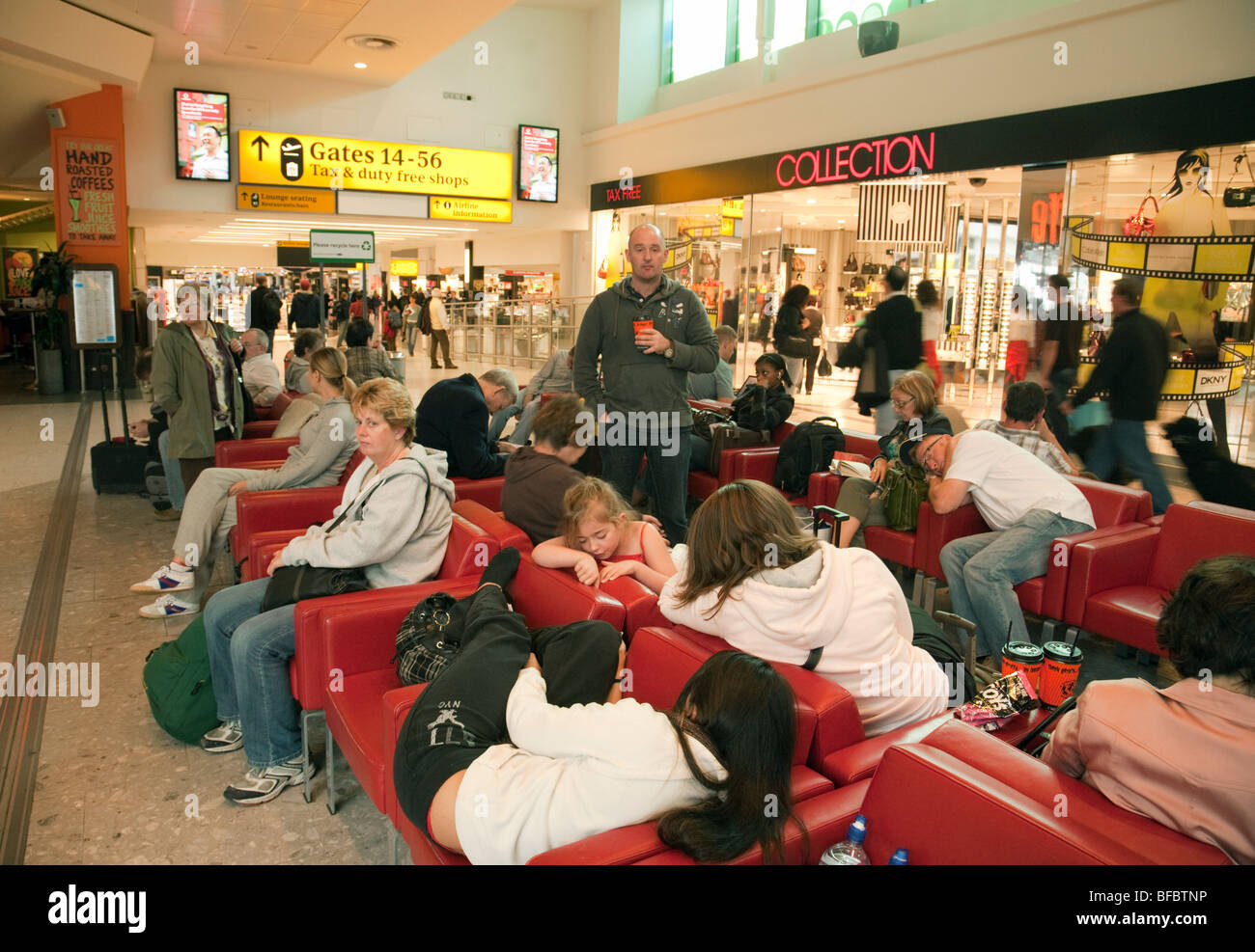 Tired airline travellers resting in the departure lounge, Terminal One, Heathrow airport, London, UK - Stock Image
