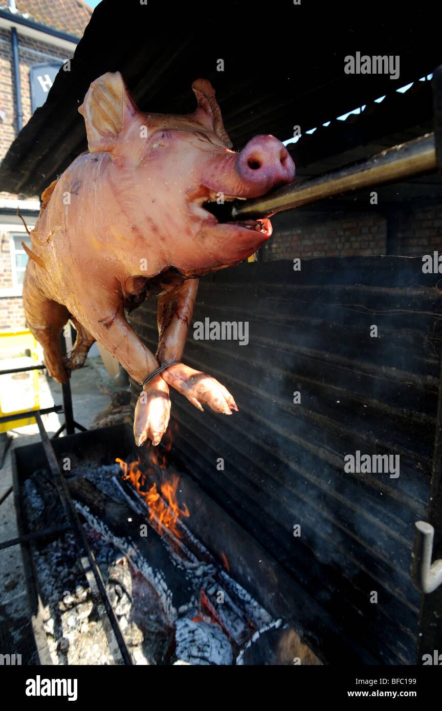 Hog roast turns on a spit - Stock Image