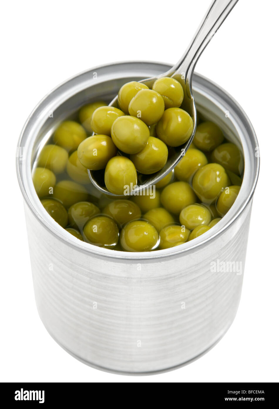 Preserved peas vegetable in metal spoon closeup - Stock Image