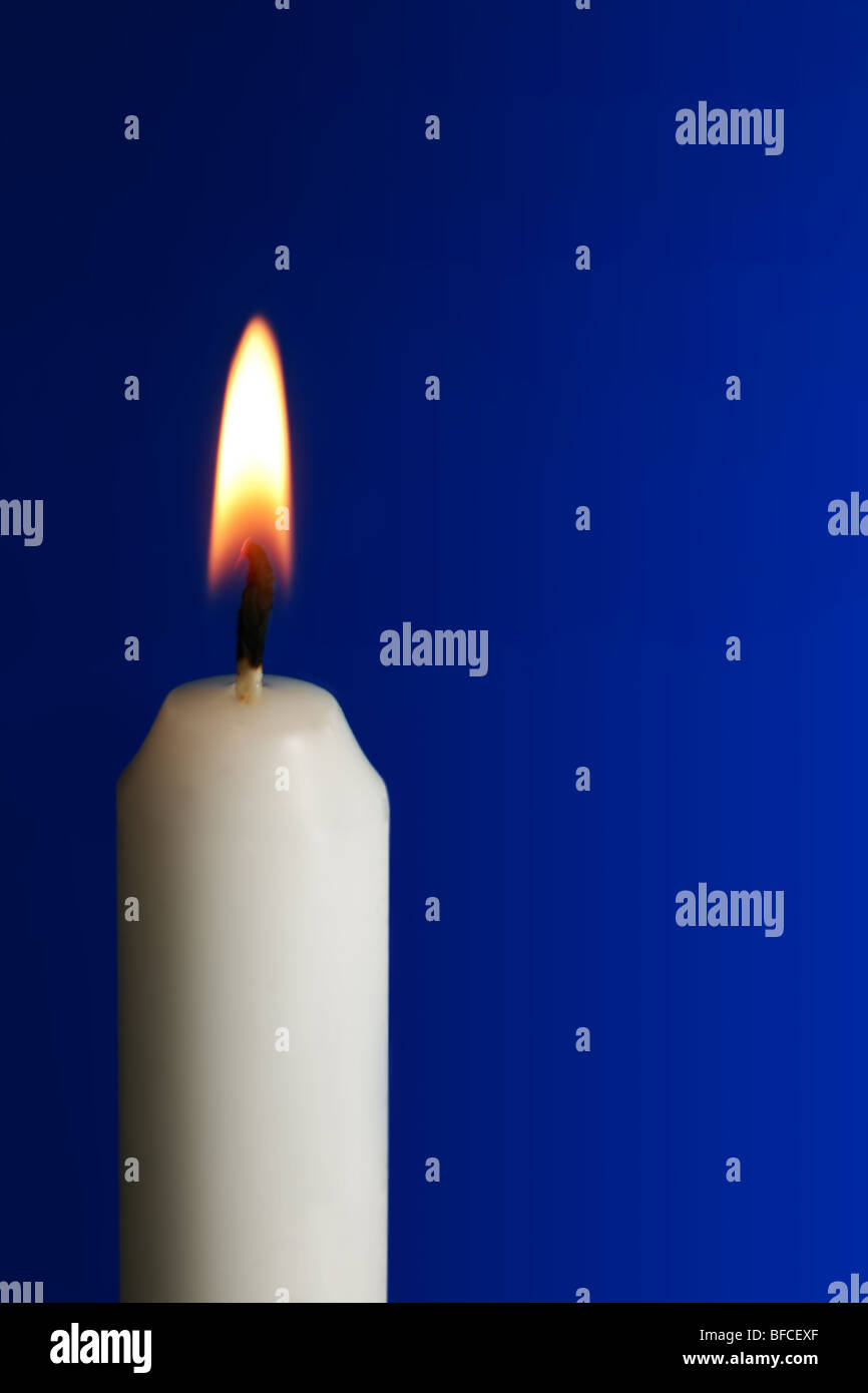 White wax candle with flame on blue background - Stock Image
