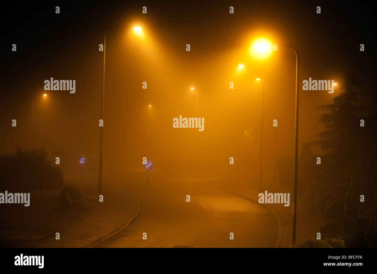 A foggy road with street lighting at night in Redditch, Worcestershire, UK - Stock Image