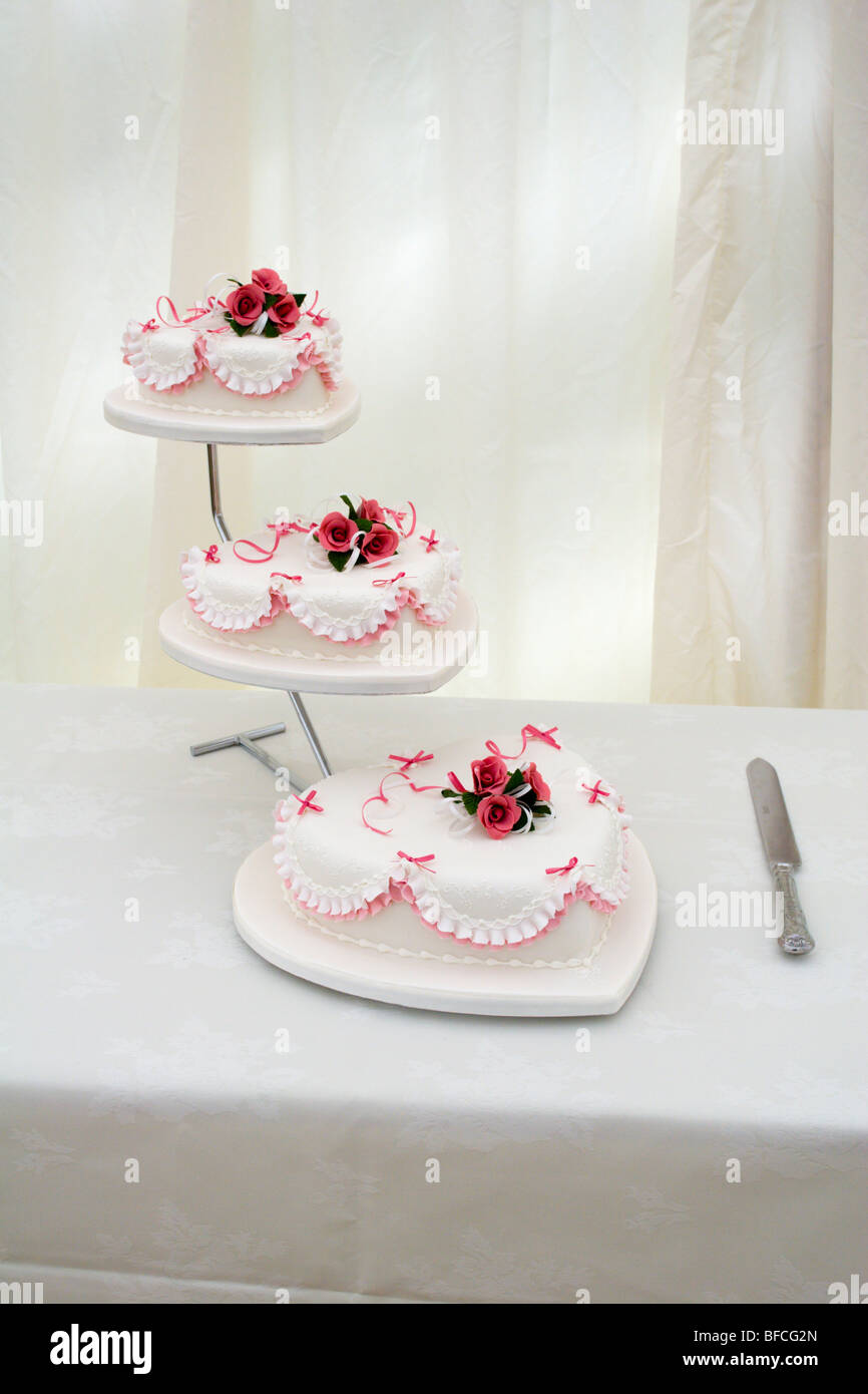 Three tier heart shaped wedding cake and knife on a table Stock ...