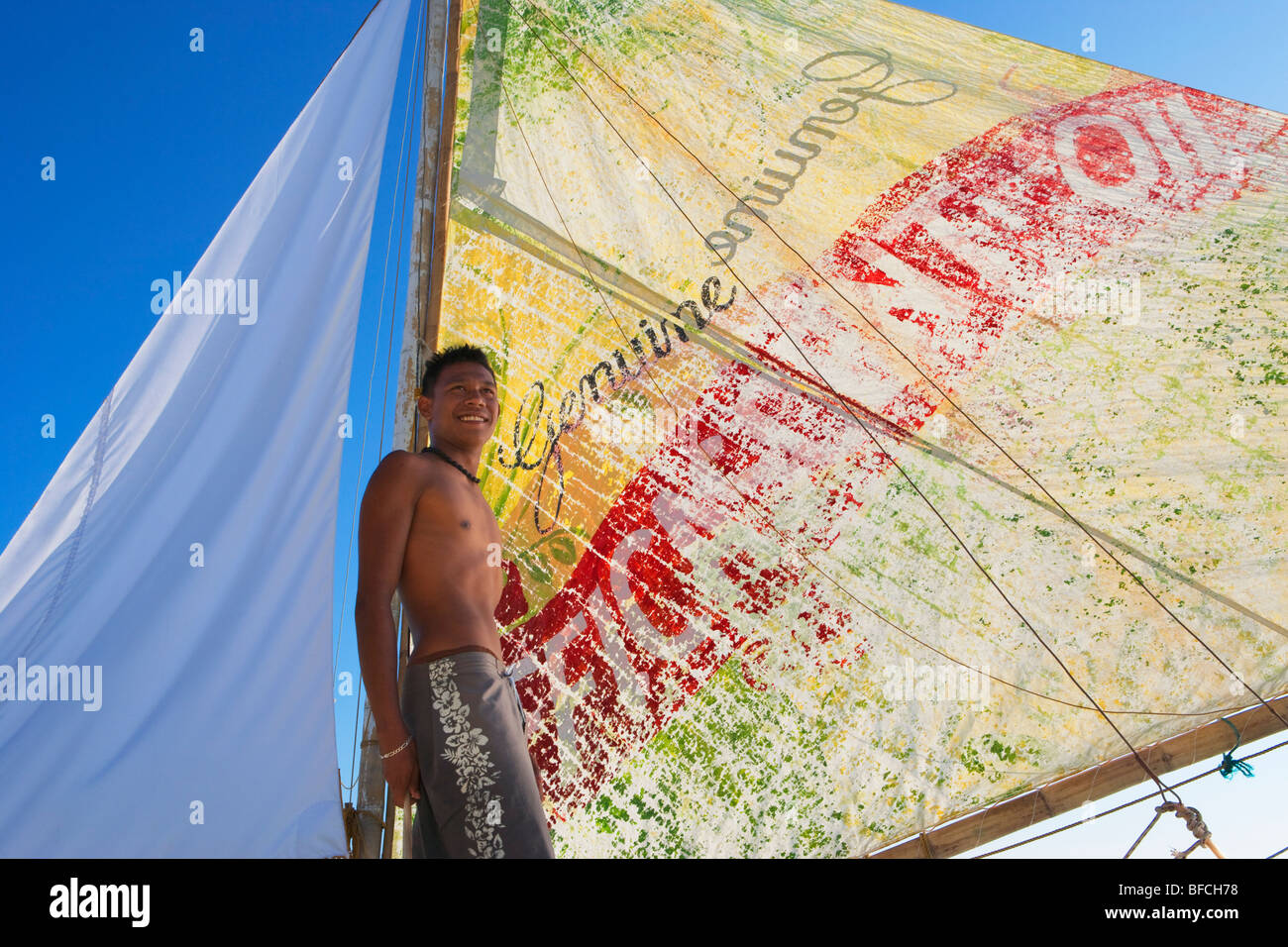 Young filipino man standing against colourful boat sail Boracay; The Visayas; Philippines. - Stock Image