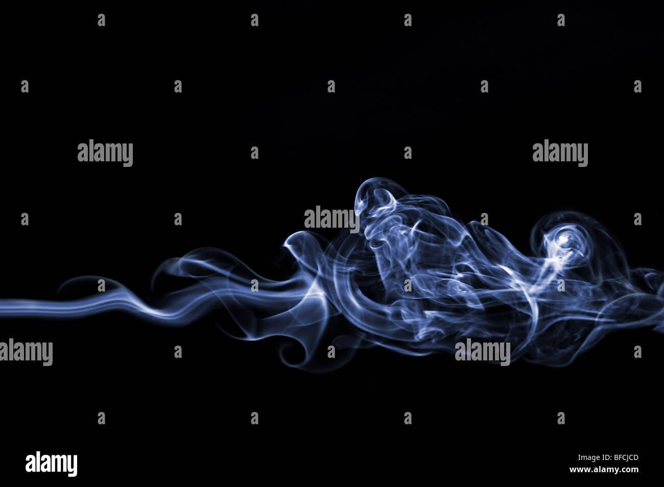 Smoke swirl on black background - Stock Image