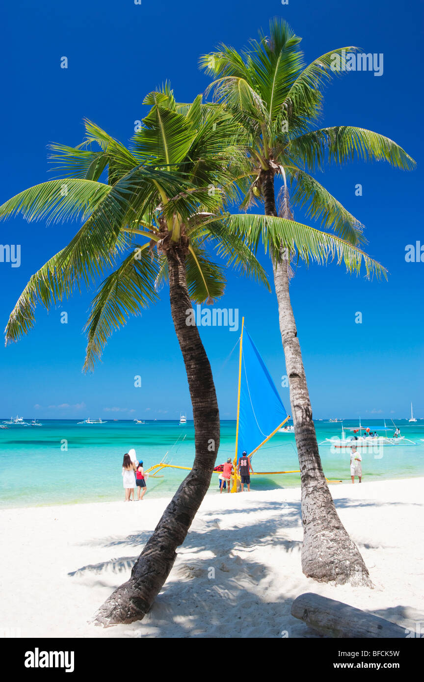 Two palm trees and sail boat Boracay; The Visayas; Philippines. - Stock Image