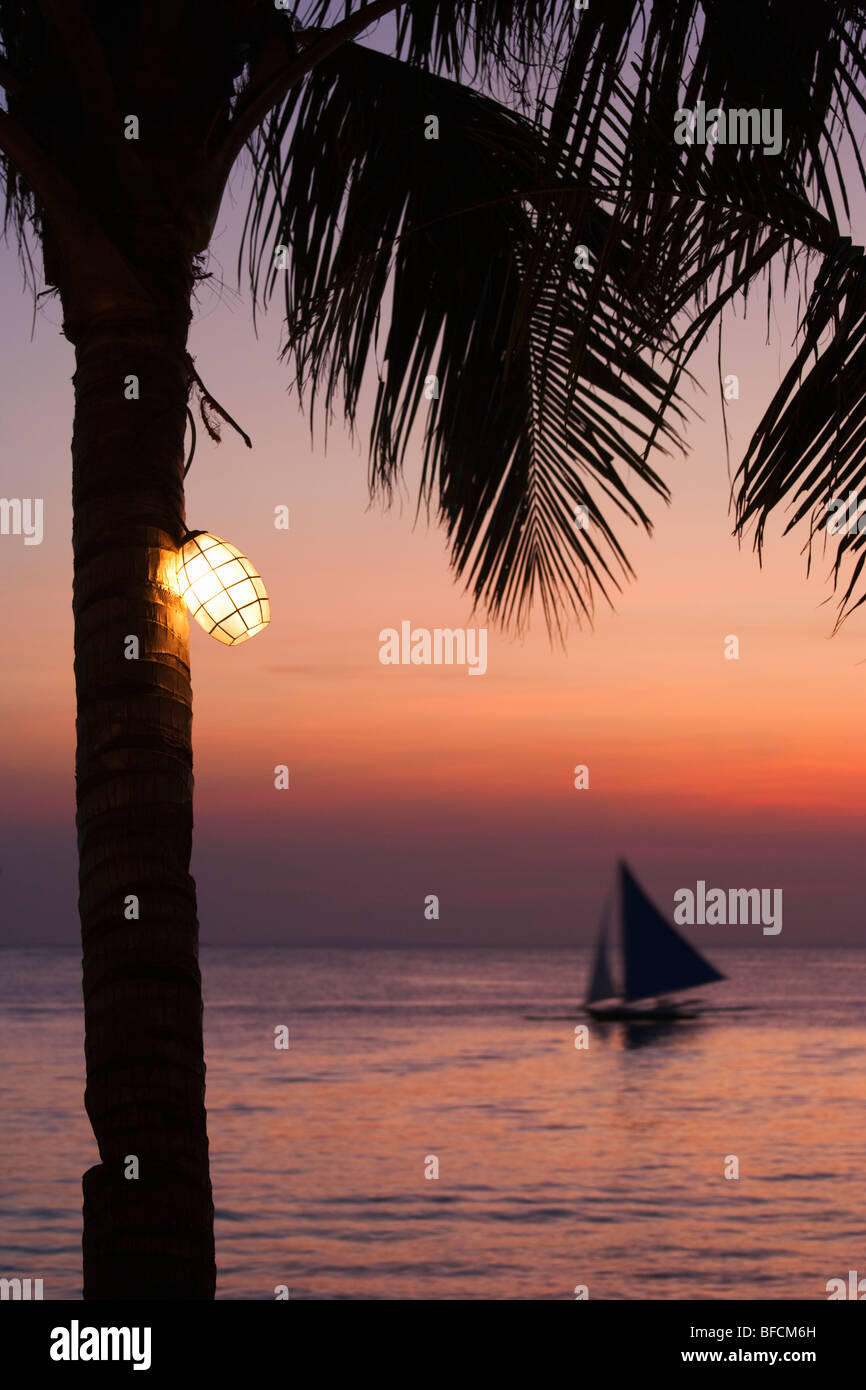 Light in palm tree at dusk and sail boat at sea Boracay; The Visayas; Philippines. - Stock Image