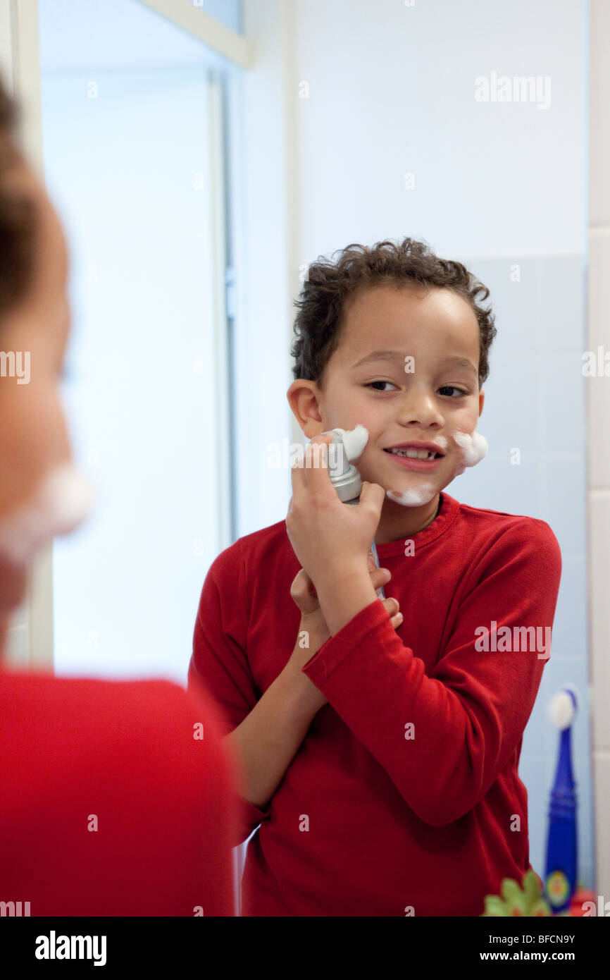 Seven year old boy is putting foam on his face - Stock Image