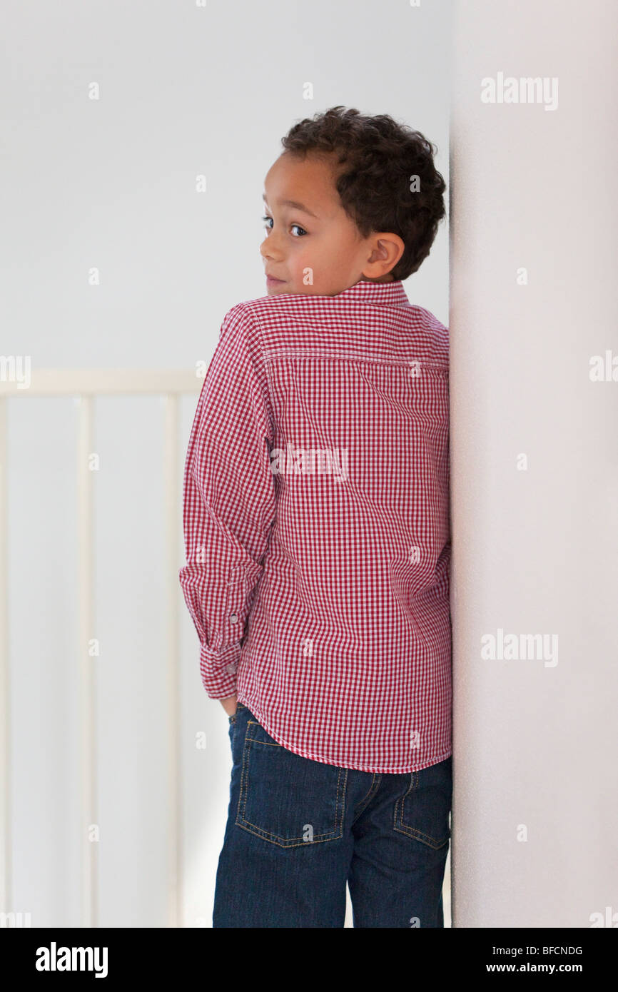 Seven year old boy leaning against the wall - Stock Image
