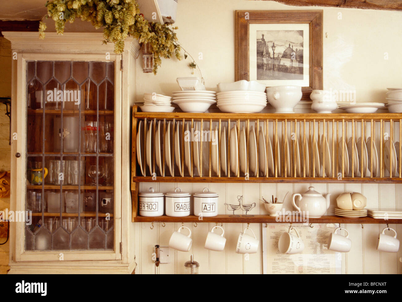 Close-up of cream bowls on wooden plate rack beside small wall cupboard in cottage kitchen & Close-up of cream bowls on wooden plate rack beside small wall Stock ...