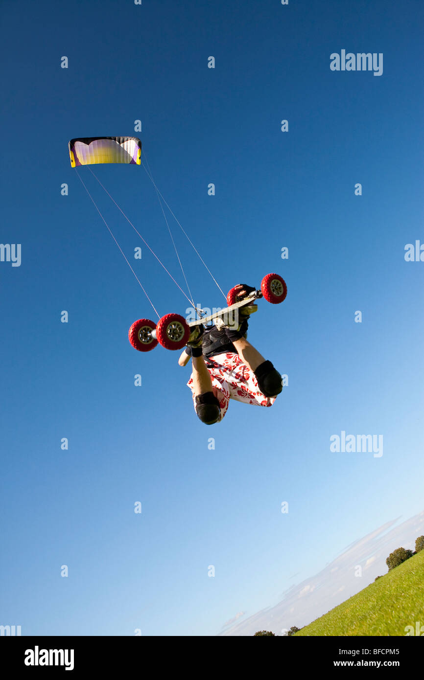 Extreme sport, freestyle kite landboarding, flying inland in open field - Stock Image