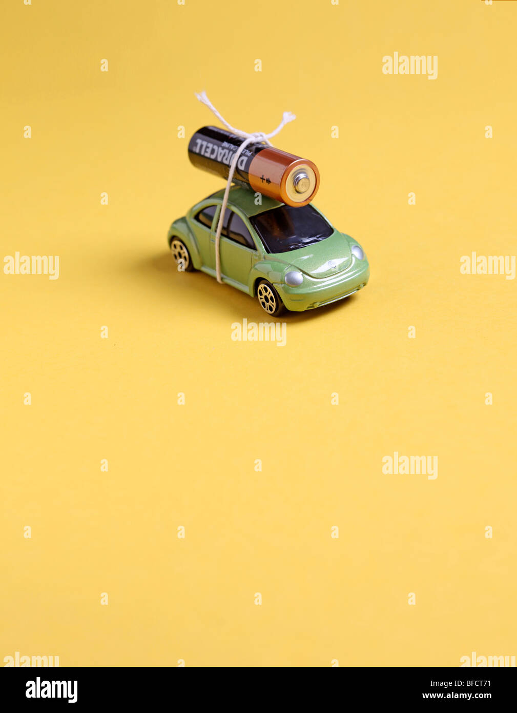 Toy car with battery tied to top with string to illustrate battery powered car and alternative green energy use. - Stock Image