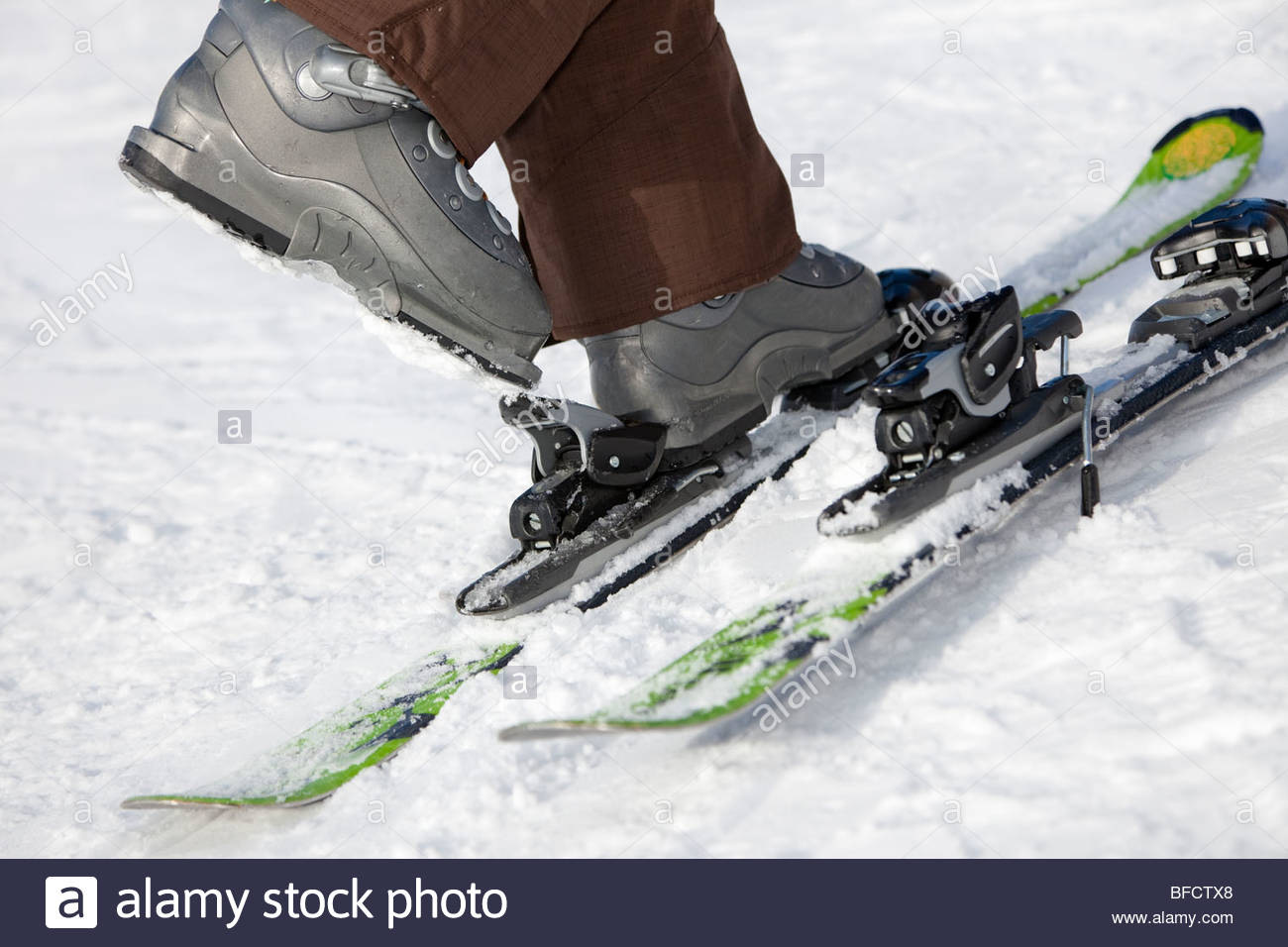 Low section view of woman unfastening her ski boots. - Stock Image