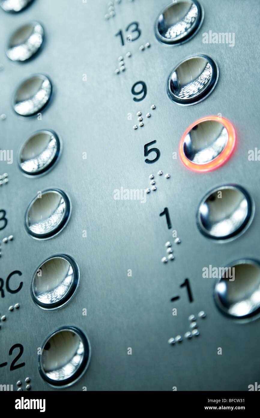 close up of elevator keypad with glowing button - Stock Image
