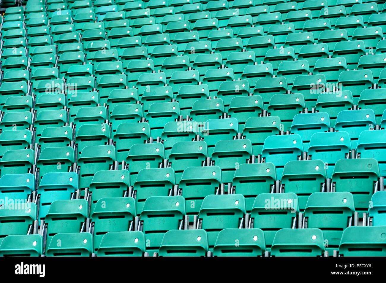 Rows of empty green seats inside a sports stadium - Stock Image