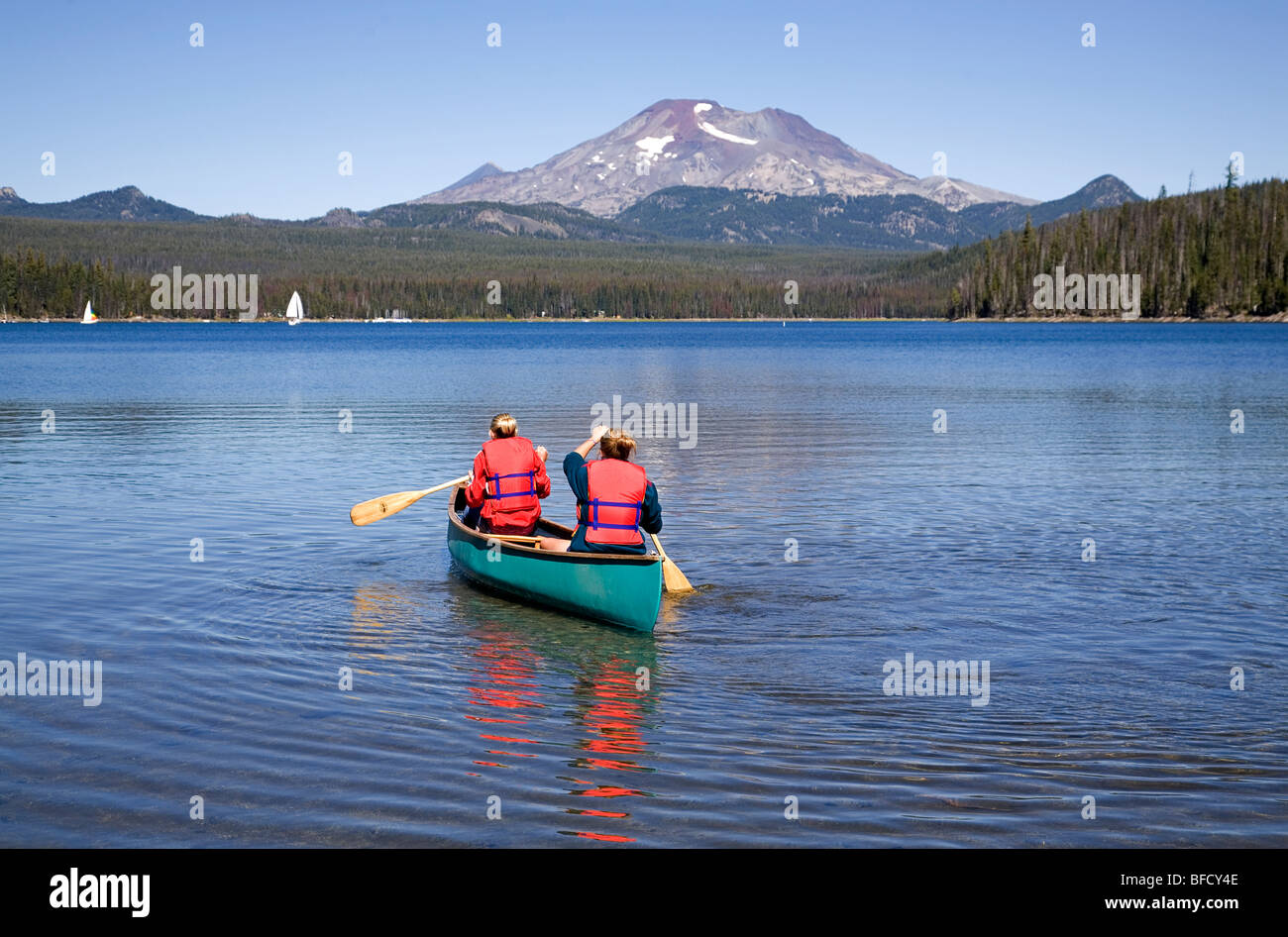 Two teenaged girls in a canoe on Elk Lake in the Oregon Cascade Mountains along the Cascade Lakes Highway - Stock Image