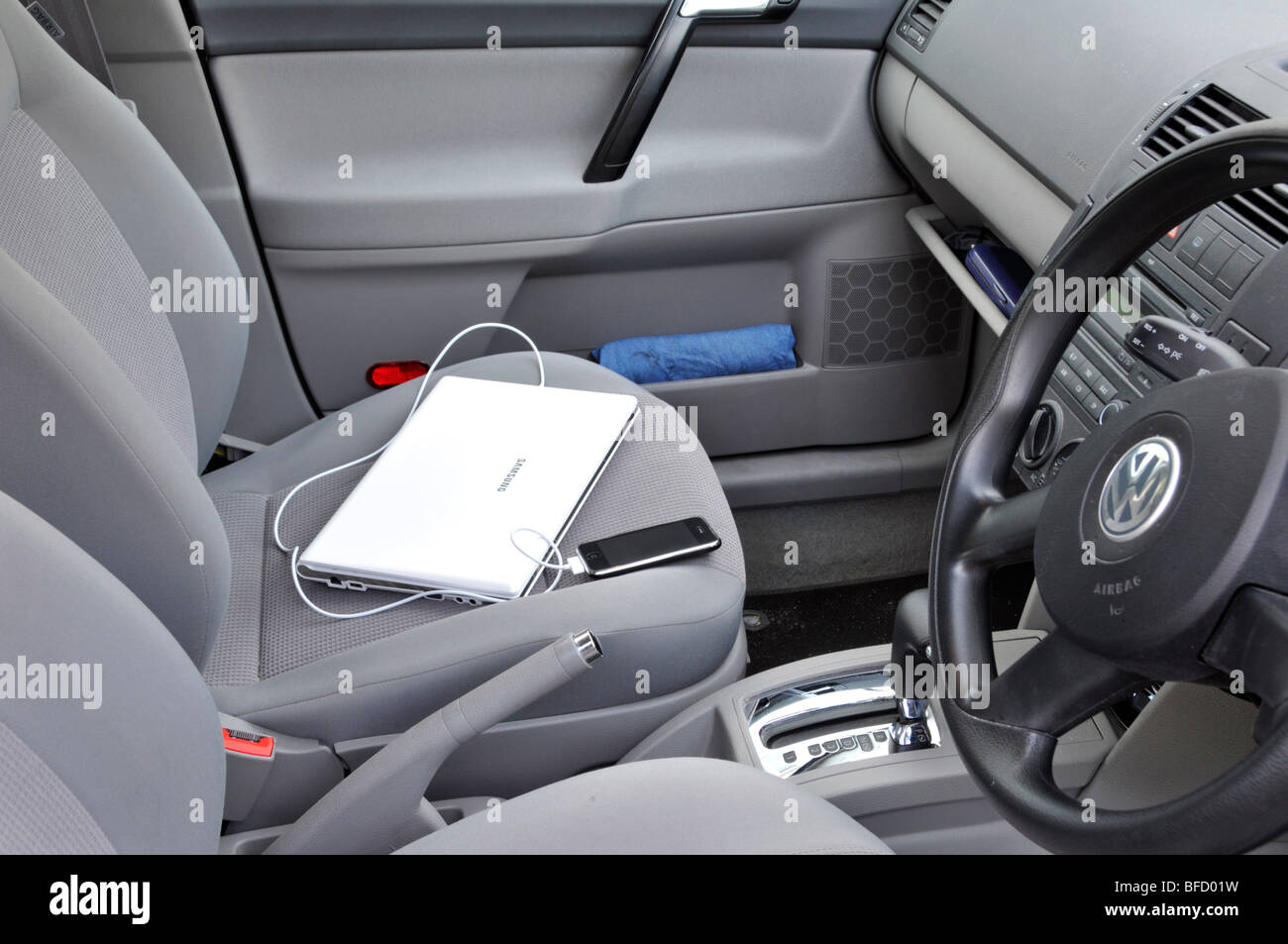 Samsung netbook and connected iphone left on passenger seat inside locked parked car - Stock Image