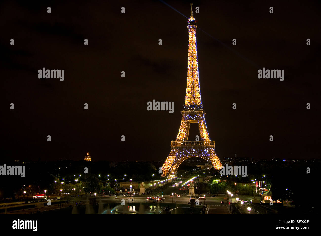 The Eiffel Tower lit up at night located on the Champ de Mars in Paris, France. - Stock Image
