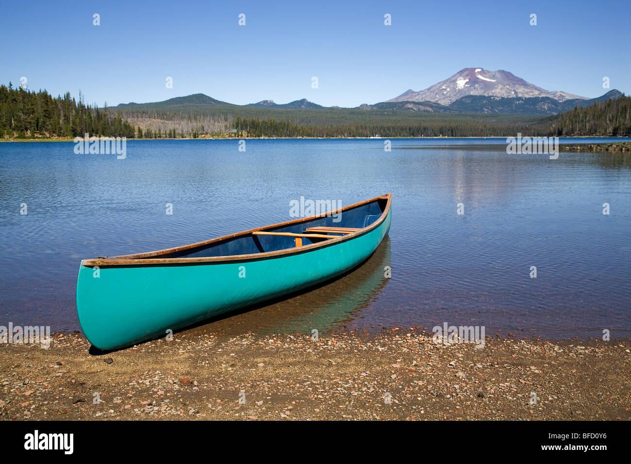 A canoe on the shore of a mountain lake in the Oregon Cascade Mountains along the Cascade Lakes Highway - Stock Image