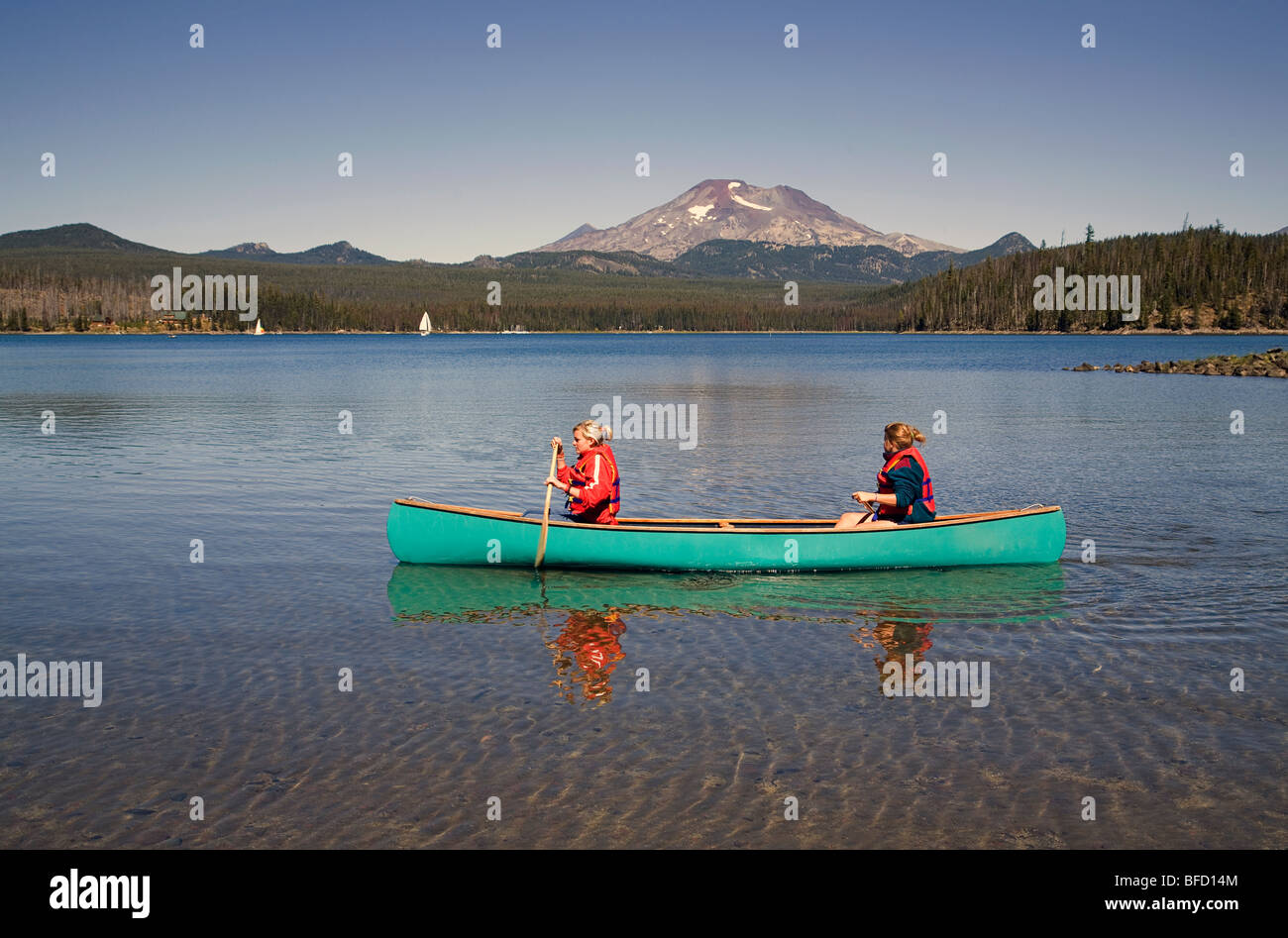 Two teen aged girls in a canoe on Elk Lake in the Oregon Cascade Mountains along the Cascade Lakes Highway - Stock Image