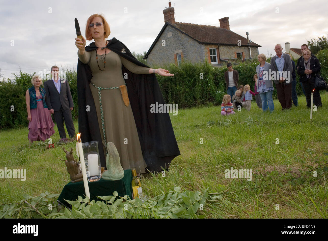 A witch in a black cloak holds a dagger up during a Pagan wedding ceremony in a field near Glastonbury in England. - Stock Image