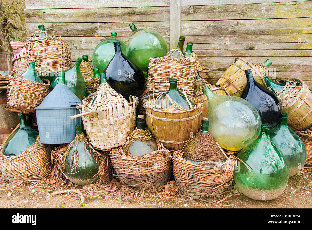 Discarded green demijohns with basket bases - Stock Image