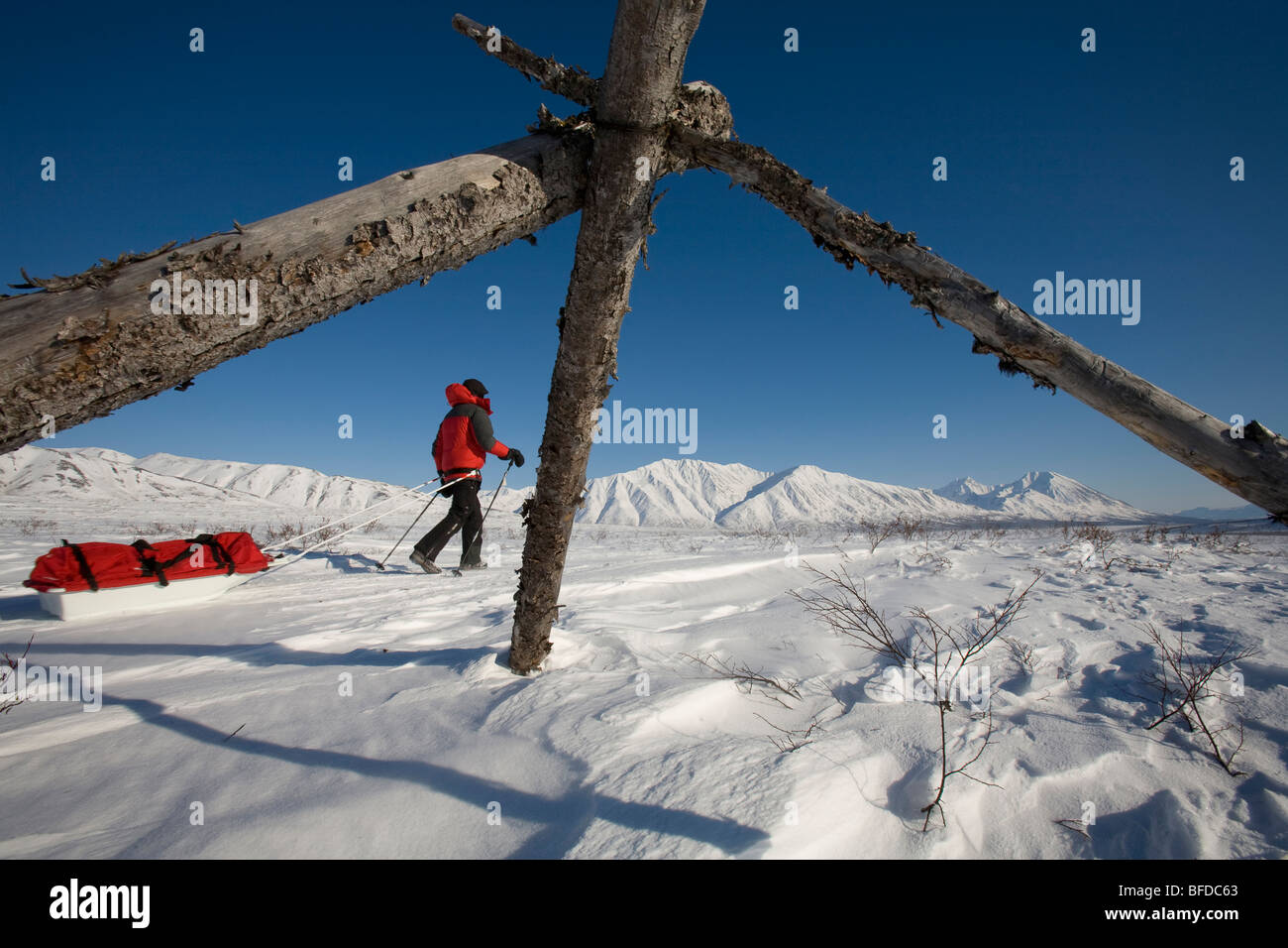 A woman hiking through a snowy, mountainous landscape pulling a sled. - Stock Image