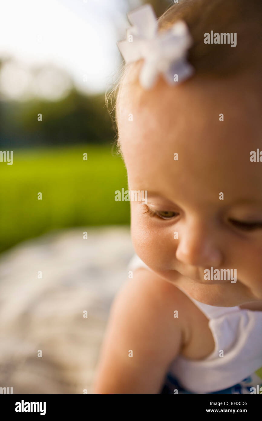 Close up view of a baby girl playing on a picnic blanket outside on a sunny day in California. - Stock Image