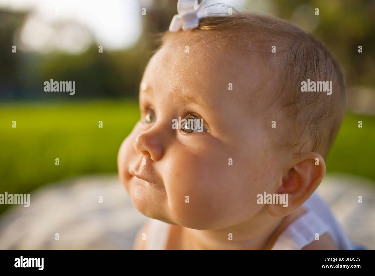 Close up view of a wide-eyed baby girl sitting on a picnic blanket outside on a sunny day in California. - Stock Image