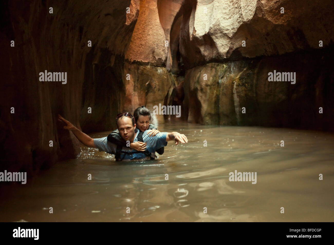 A couple wades through a cold pool in a slot canyon in Utah. Stock Photo