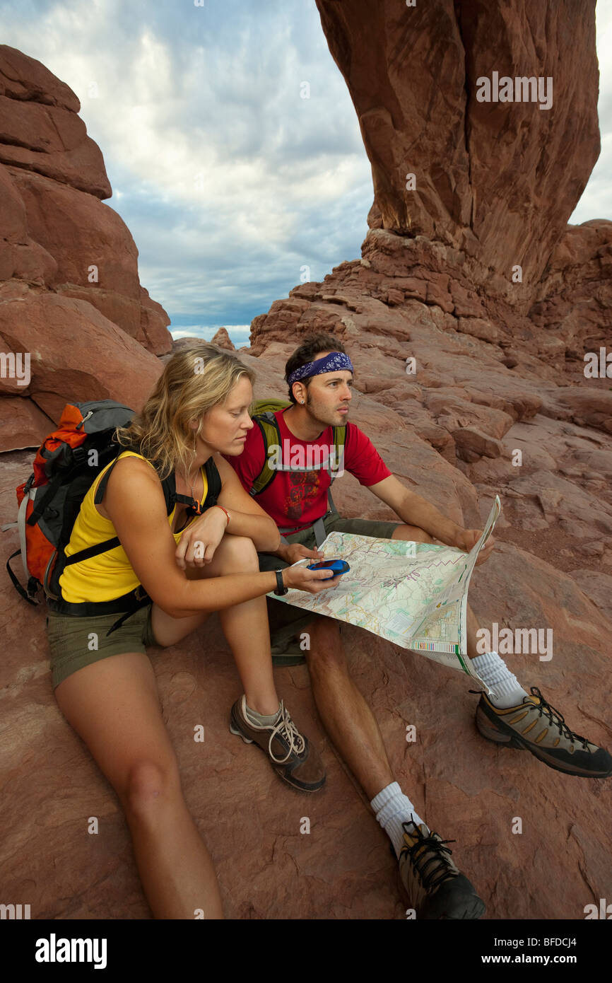 A couple siting down in front of an arch using a GPS and a map in Arches National Park, Utah. - Stock Image