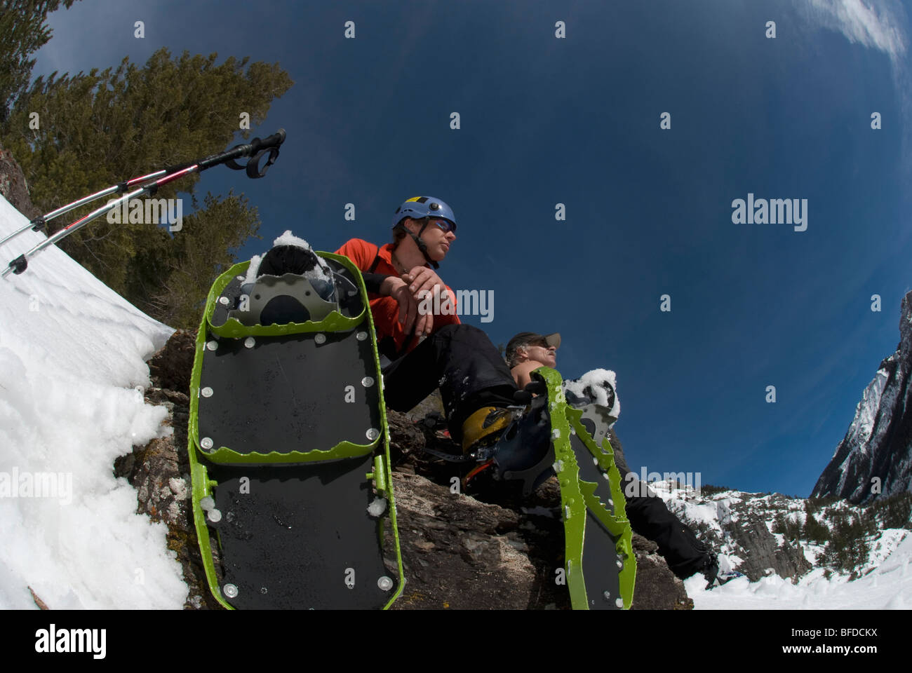 Two men rest under blue skies while snowshoeing near Ouray, Colorado. - Stock Image