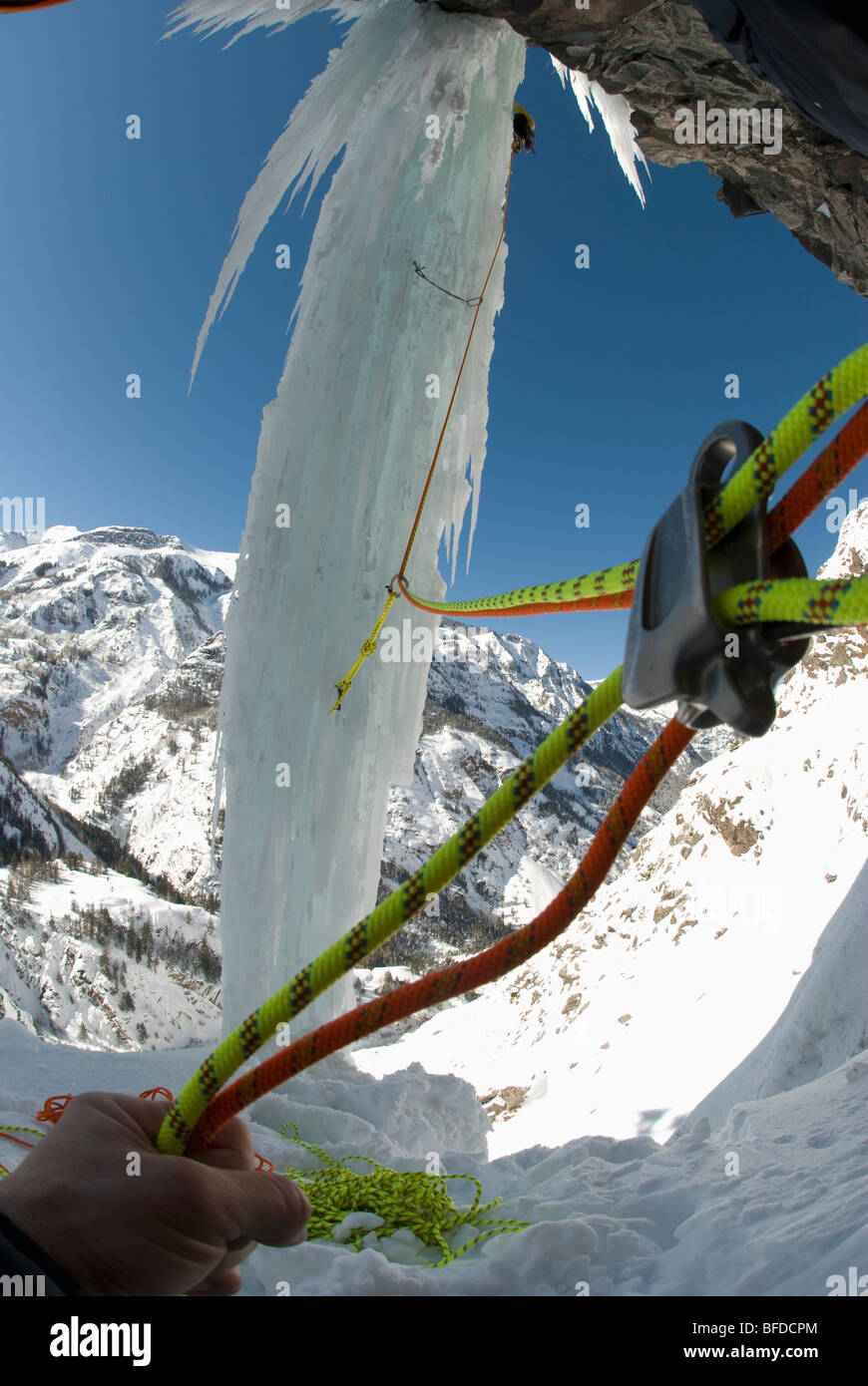 View of climbing rope used by a professional male ice climber as he ascends a frozen waterfall pillar. - Stock Image