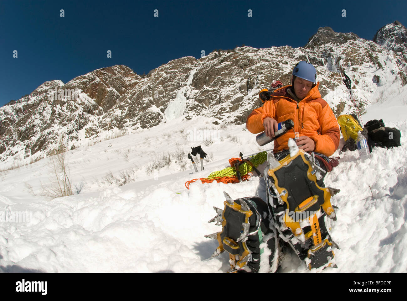 A young man drinking warm tea from a thermos while ice climbing near Ouray, Colorado. - Stock Image