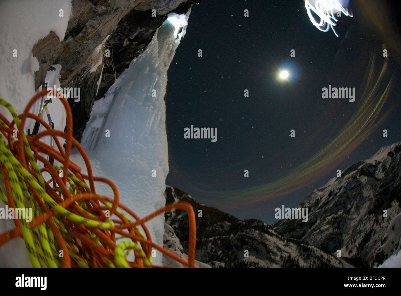 Night view of ropes as a young man ice climbs with a headlamp under a full moon. - Stock Image