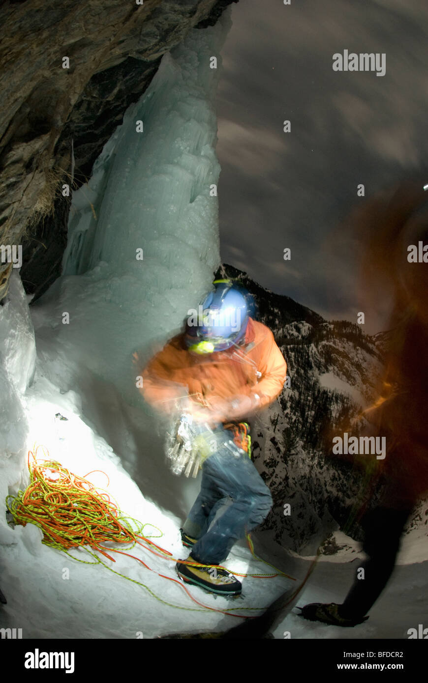 A young man prepares for ice climbing at night with a headlamp near Ouray, Colorado. - Stock Image