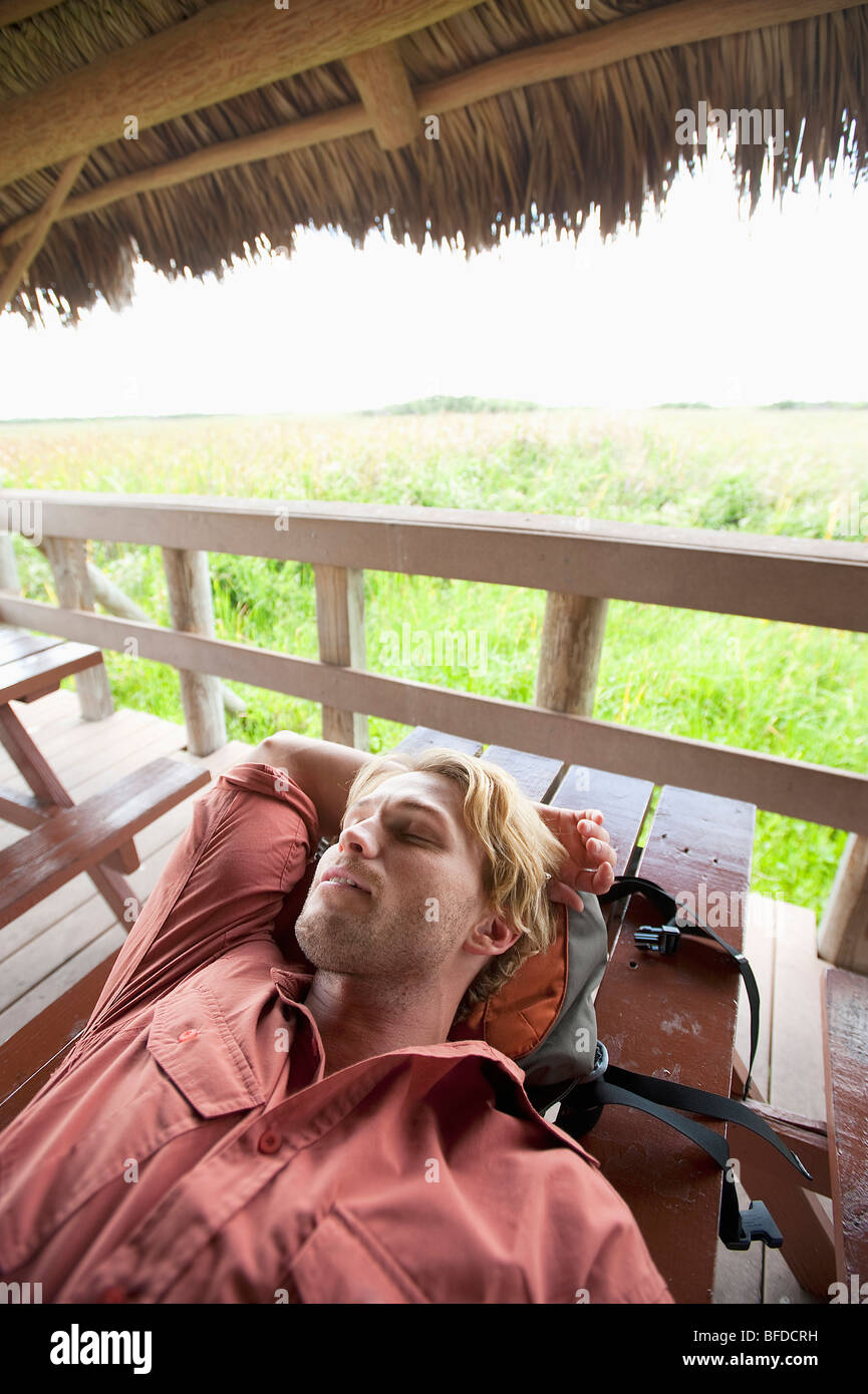 A man naps under a thatched roof in Everglades National Park, Florida. - Stock Image